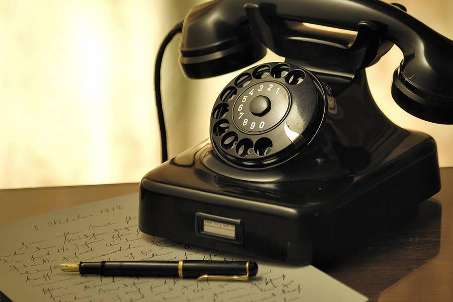 Telefon stacjonarny starego typu z tarczą do wykręcania numeru.