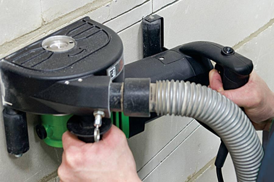 Praca na elektrycznej bruzdownicy do betonu. Do bruzdownicy podłączony jest odkurzacz.
