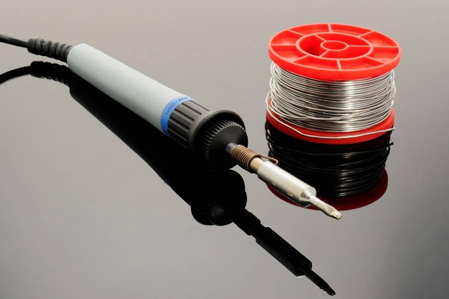Lutownica wraz z cyną. Cyna dostępna jest w zwojach o różnej średnicy drutu.