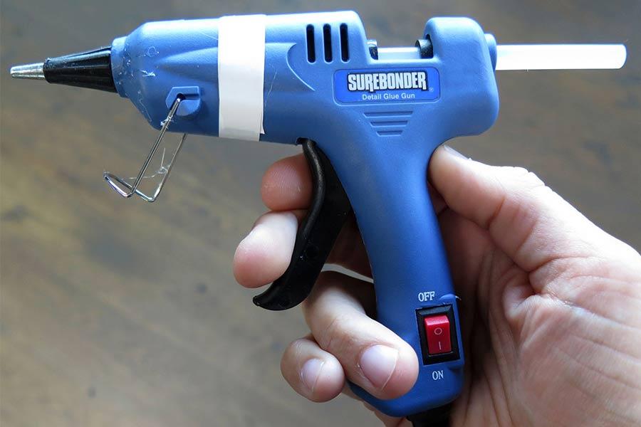 Elektryczny pistolet do kleju wraz z zamocowaną laską kleju.