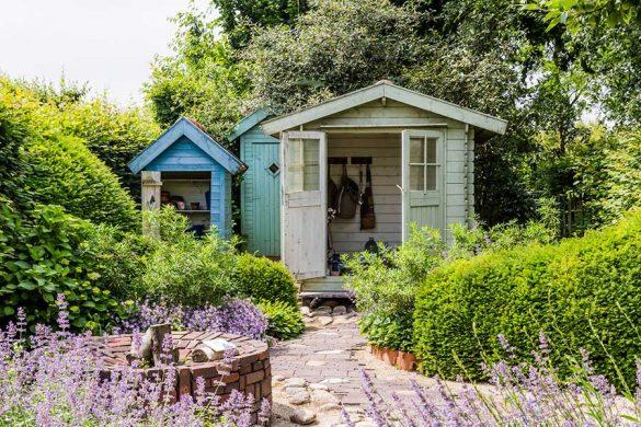 Drewniany domek ogrodowy na narzędzia z dobudówką. Bardzo popularny sposób przechowywania narzędzi ogrodowych.